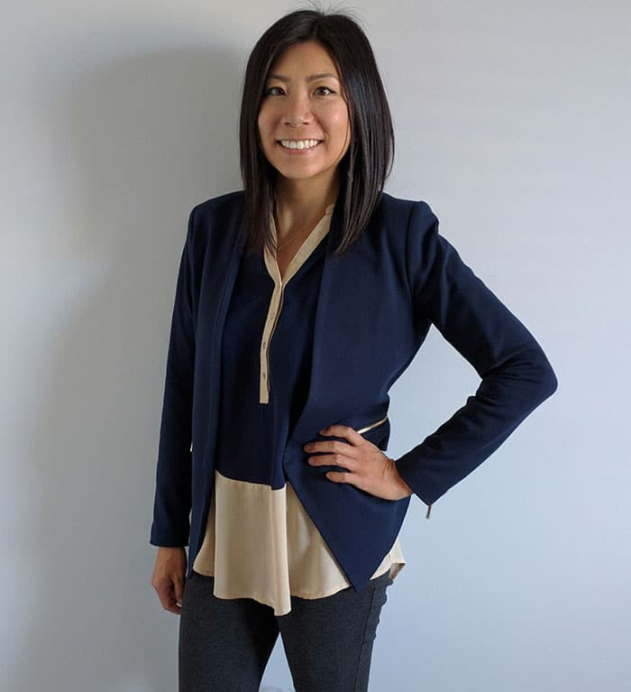 Smiling woman standing with one hand on hip.